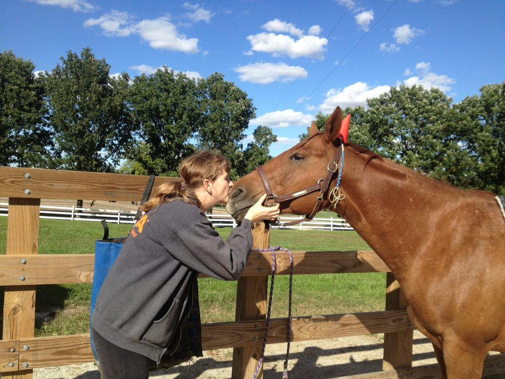 Trish McMillan - Equine Behavior Specialist kissing a horse